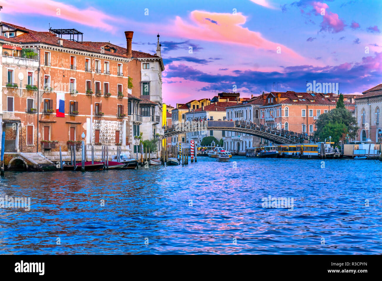 Colorful Ponte dell Academia Bridge. Sunset ferry docks, Grand Canal, Venice, Italy - Stock Image