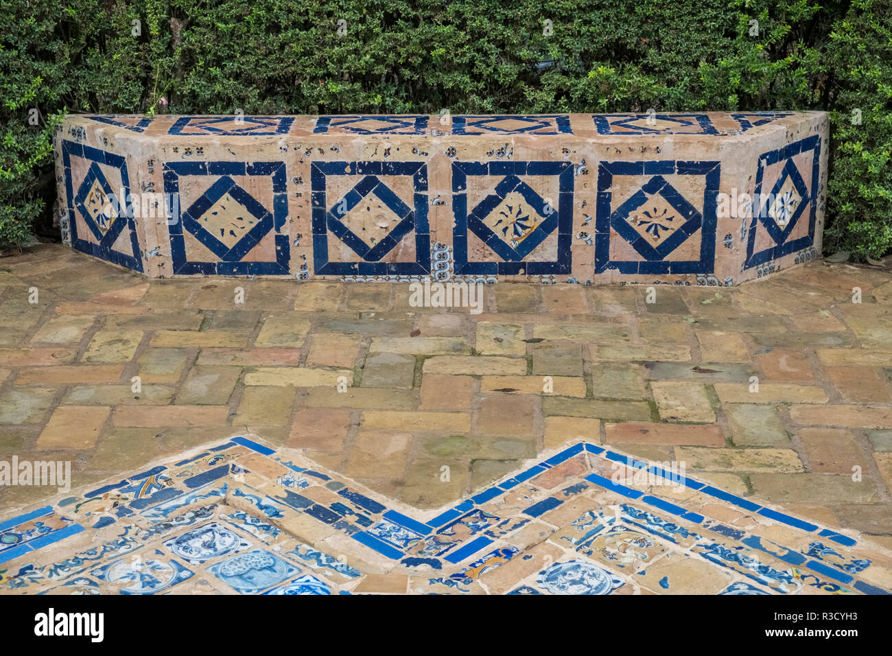Ornate decorative ceramic tiles used for a small seating area in the Real Alcazar, Seville, Andalucia, Spain - Stock Image