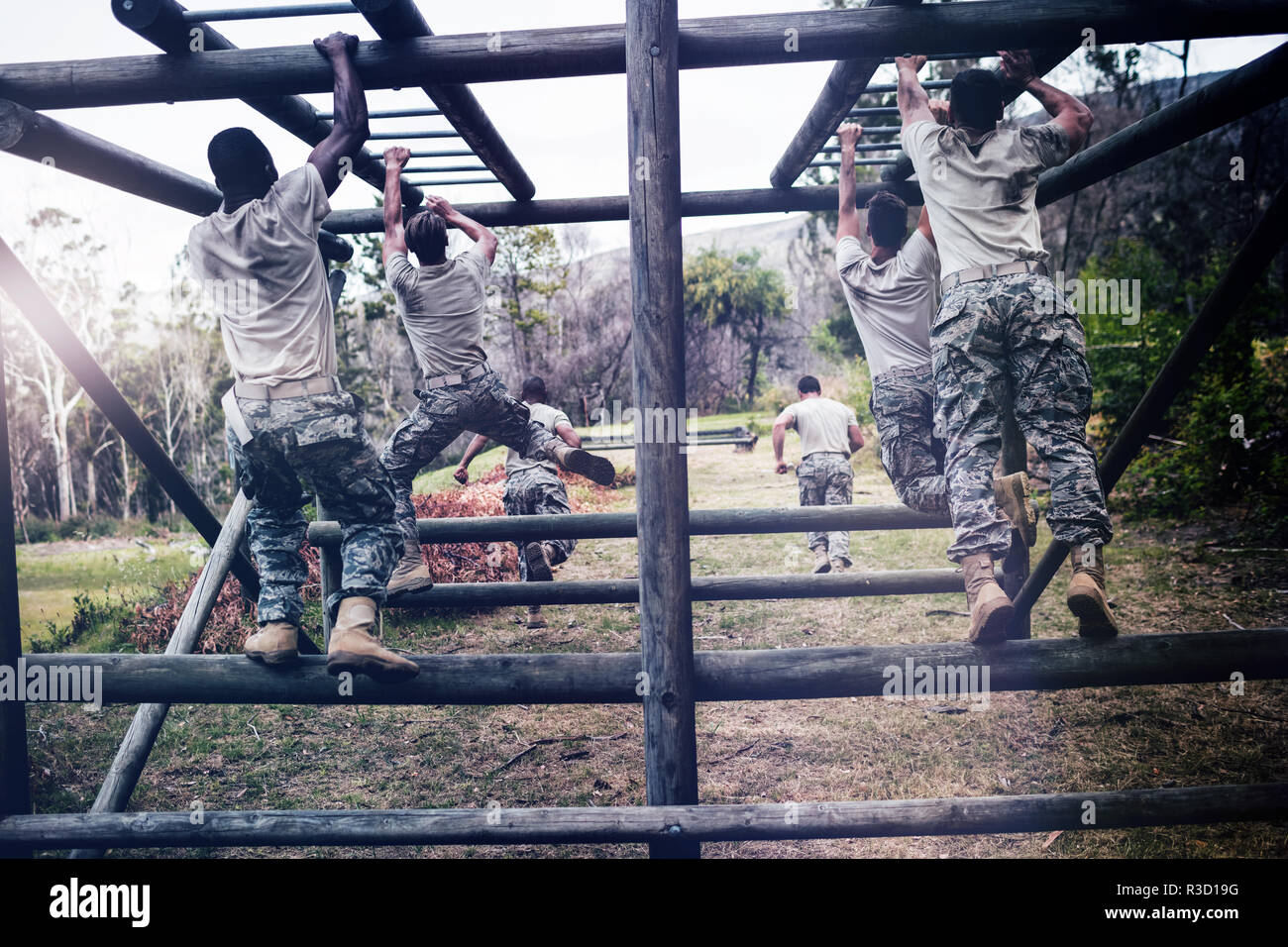 Soldiers climbing monkey bars - Stock Image