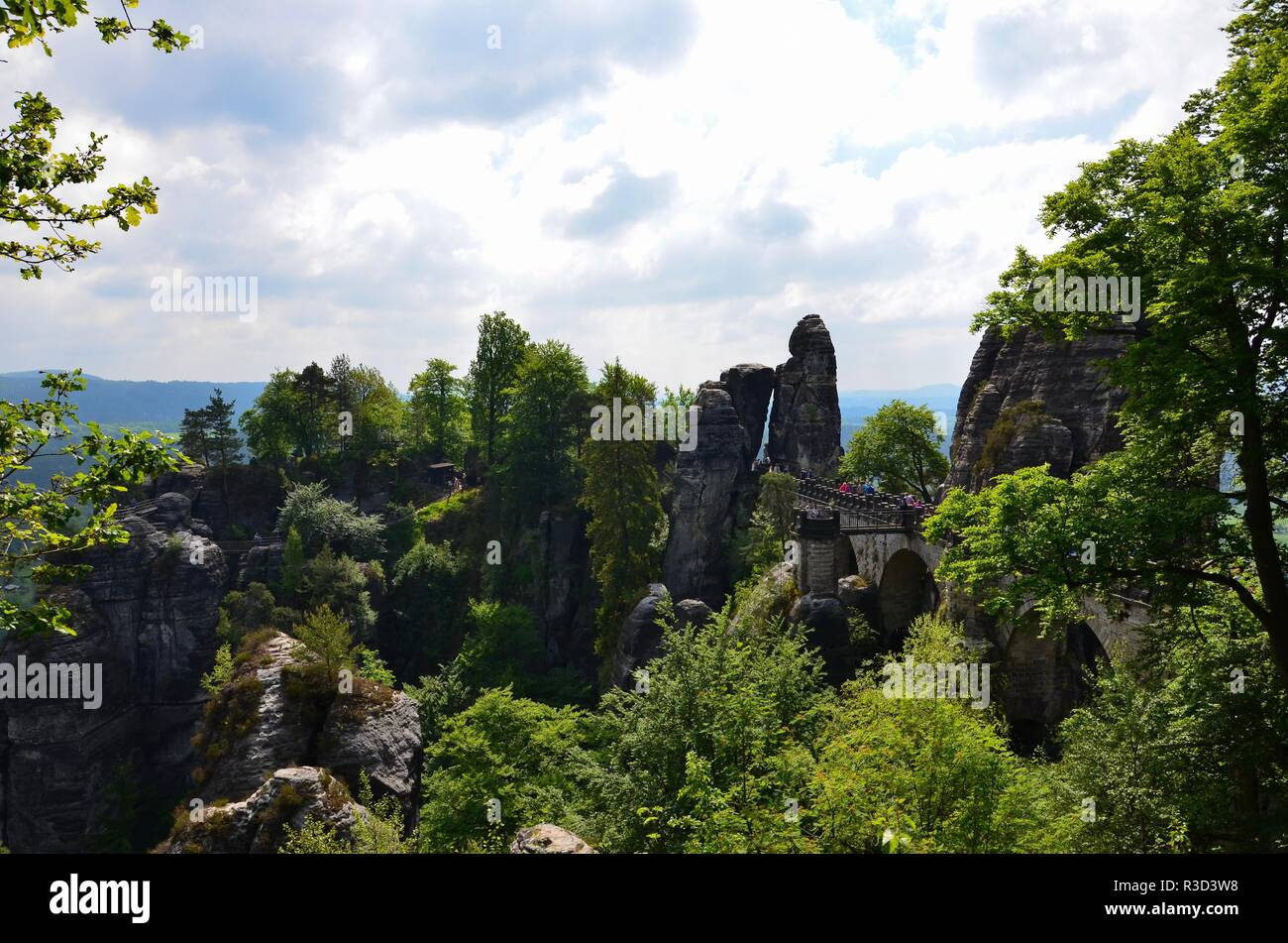 The mountain range Elbe Sandstone Mountains (Elbsandsteingebirge) near the town of Rathen in Saxony in Germany, people crossing the old bastion bridge Stock Photo
