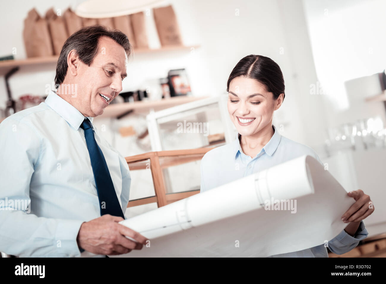 Optimization plan. Nice positive people discussing their business while looking at the drawing - Stock Image