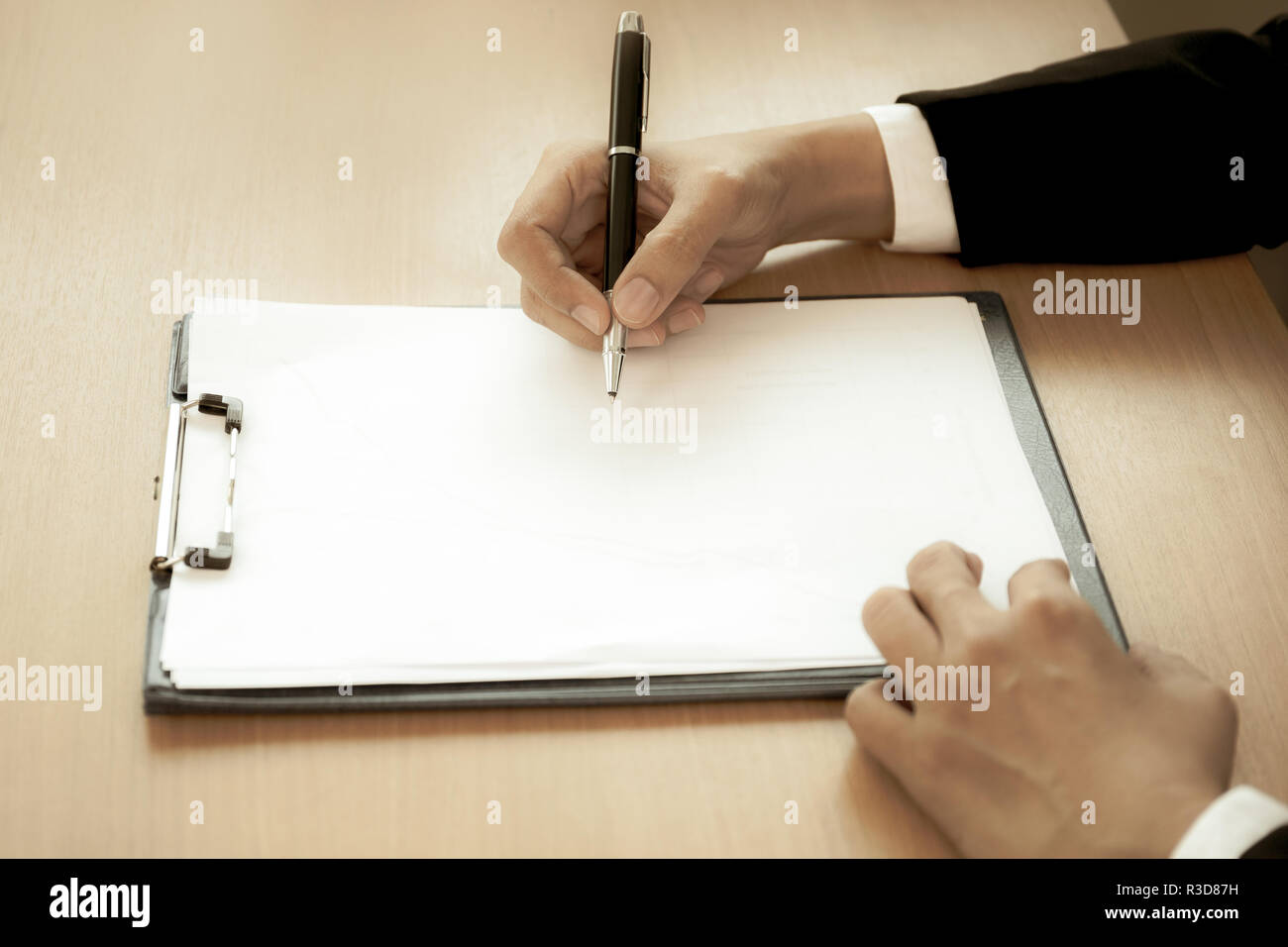 Businessman at office desk signing a contract form in creative aged photo. - Stock Image