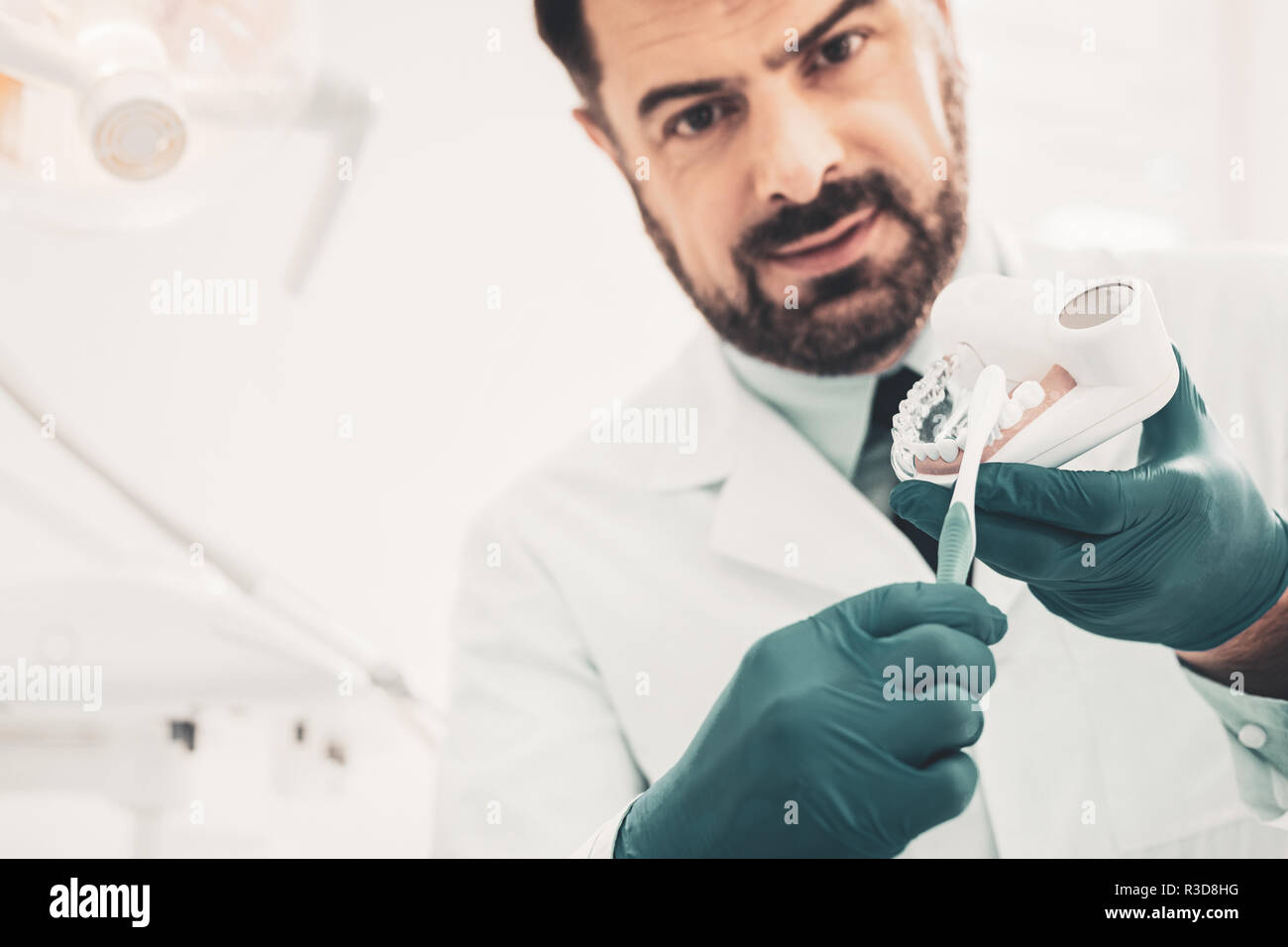 Proper teeth cleaning. Close up of serious doctor with toothbrush and dental model standing in front of you while explaining rules of right teeth brus - Stock Image