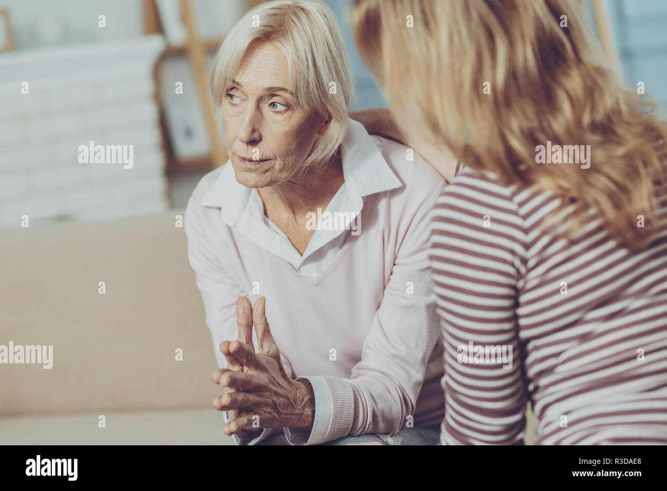 Disheartened. Concerned elderly woman sitting in bright room in front of her caring daughter while looking thoughtfully into the distance - Stock Image