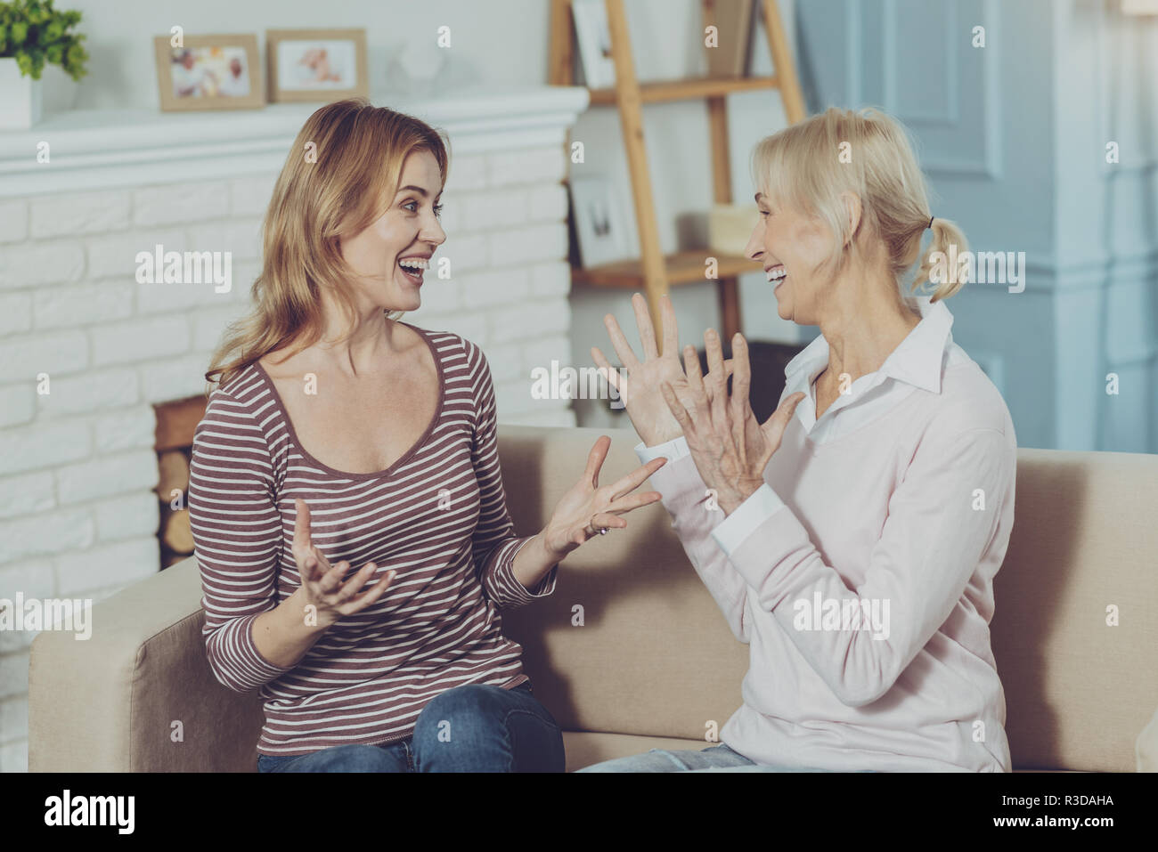 Uncontrollable joy. Cheerful senior mother with her happy young daughter feeling joy after getting very good news while resting on couch in living roo - Stock Image