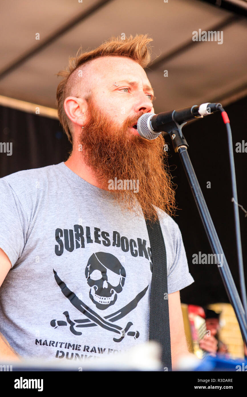 Faversham Hop Festival 2018, Sur Les Docks, French rock Folk group on stage. Group member, Guitch, singing into microphone while on stage. - Stock Image