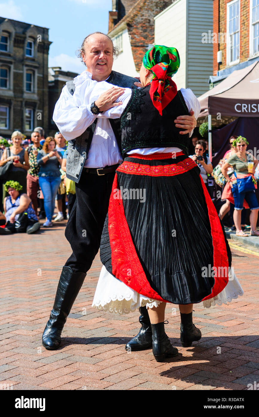 Faversham Hop Festival 2018, senior Hungarian man and woman in traditional costume dancing waltz style in front of audience in town street. Stock Photo