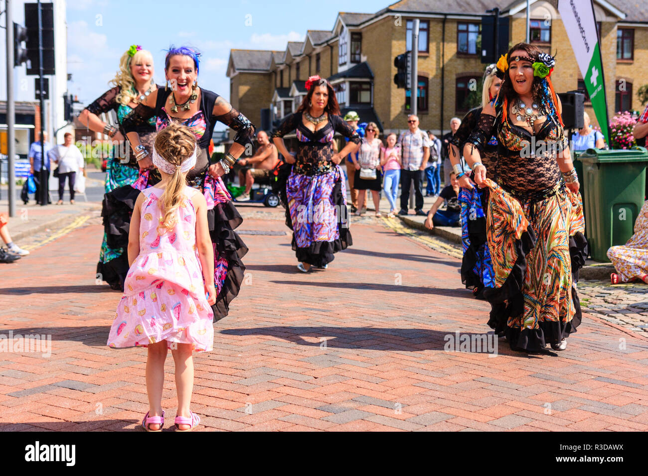 Faversham hop festival. Anaconda Dance group belly dancing in town street with little girl standing in front of them determined not to let them pass. - Stock Image