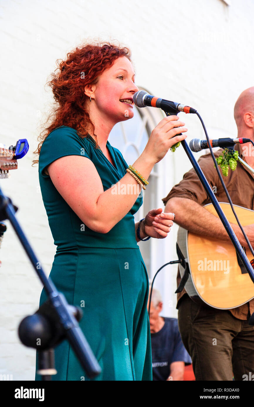 Faversham Hop Festival 2018. Young woman with red hair, Heather Grabham from the folk group Faran Flad, singing into microphone outdoors on stage. - Stock Image