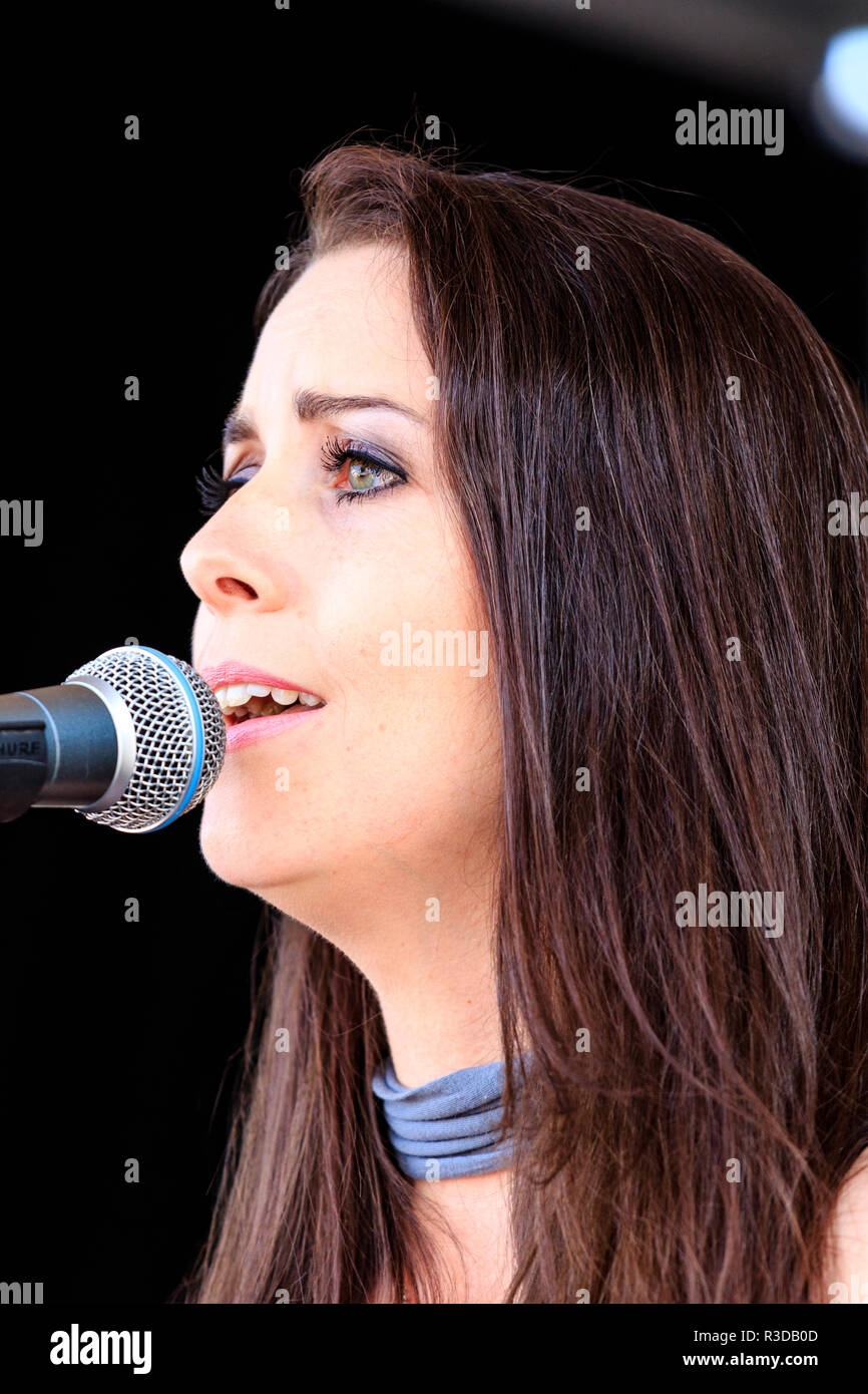 Close up of Chloe Elizabeth Hunter from the Indie rock group, Feral Ghost, singing into microphone while on stage at Faversham Hop festival. - Stock Image