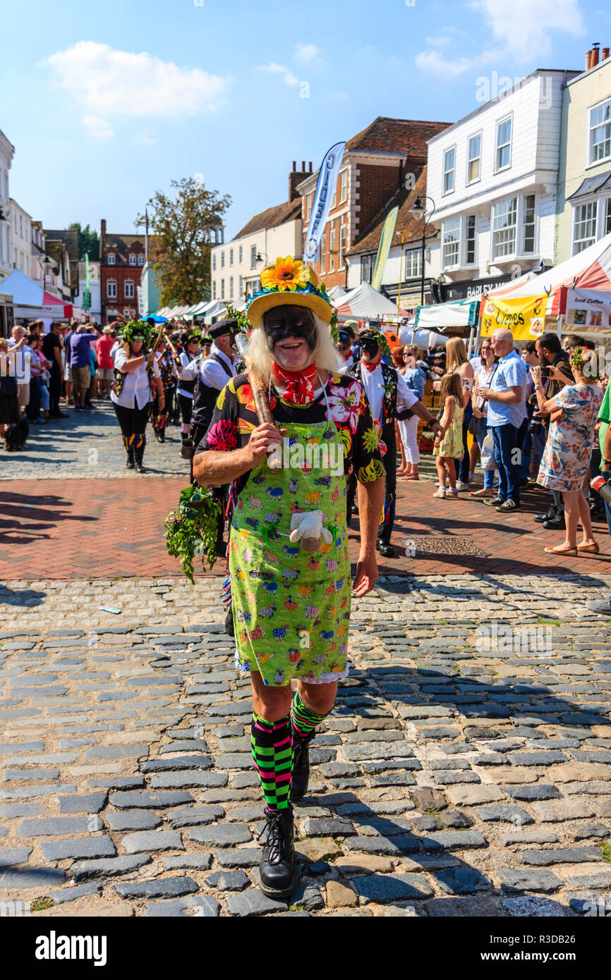 Faversham hop festival. Parade, Dead Horse and the Broomdashers Morris, with blacked faces, walking towards viewer along street lead by a Morris fool. - Stock Image