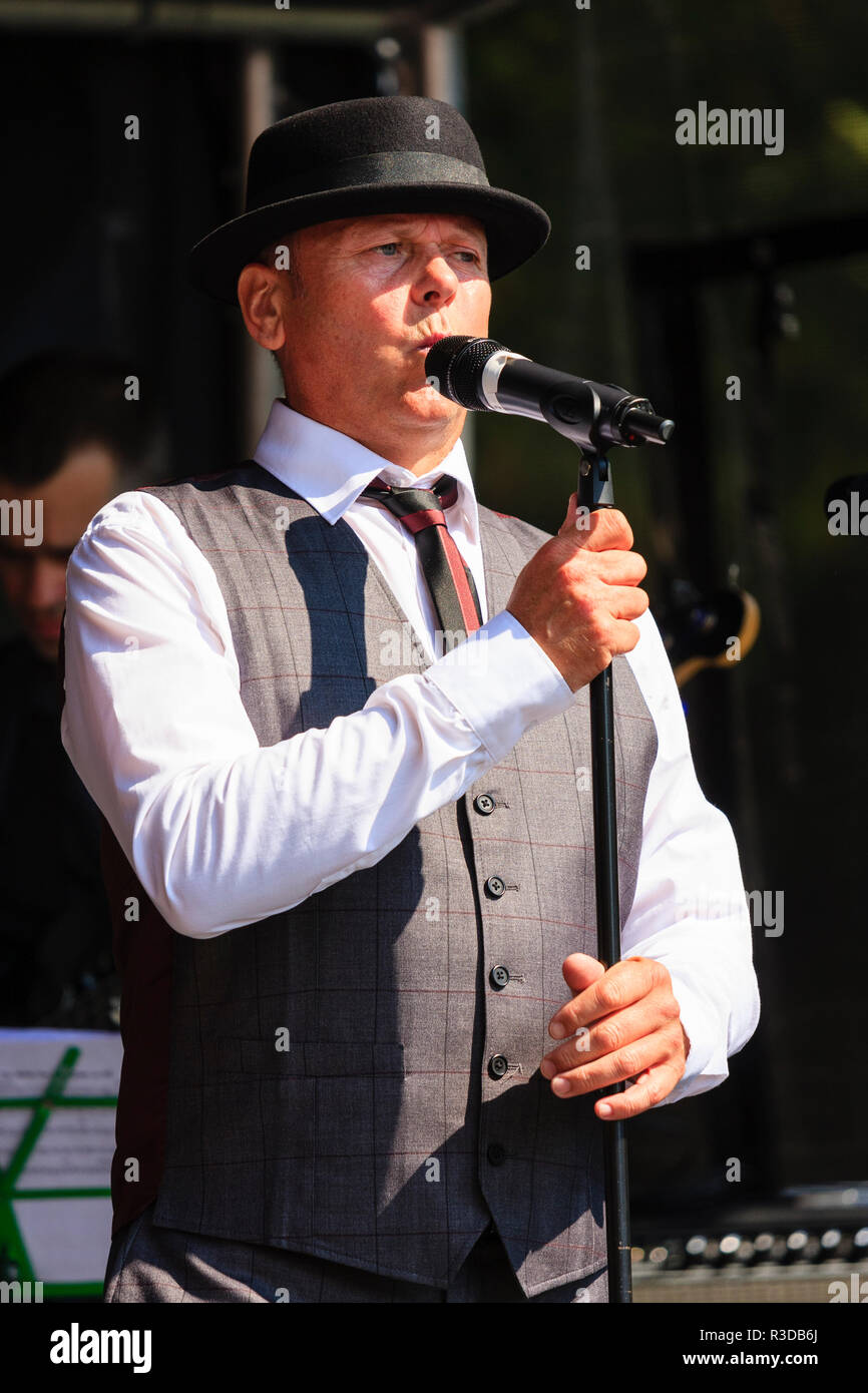 Faversham Hop Festival 2018, vintage Swingtime band Goosebumps on stage. Man, Mark Churchward, lead vocalist, singing, wearing hat. waistcoat and tie. - Stock Image