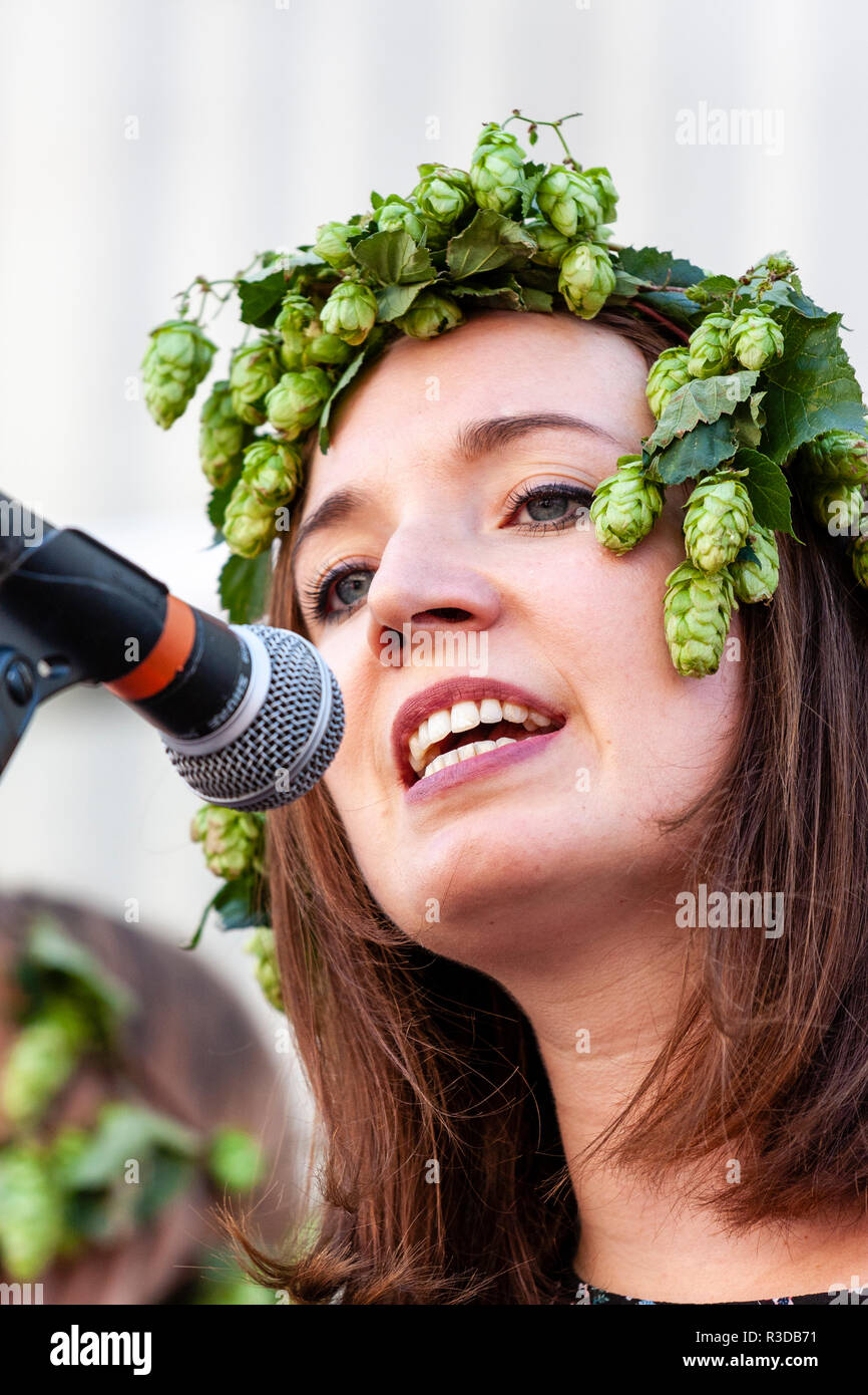 Faversham Hop Festival 2018, Blue Grass folk band Mockingbird. Close up. Caucasian woman singing into microphone while wearing hops around her head. - Stock Image