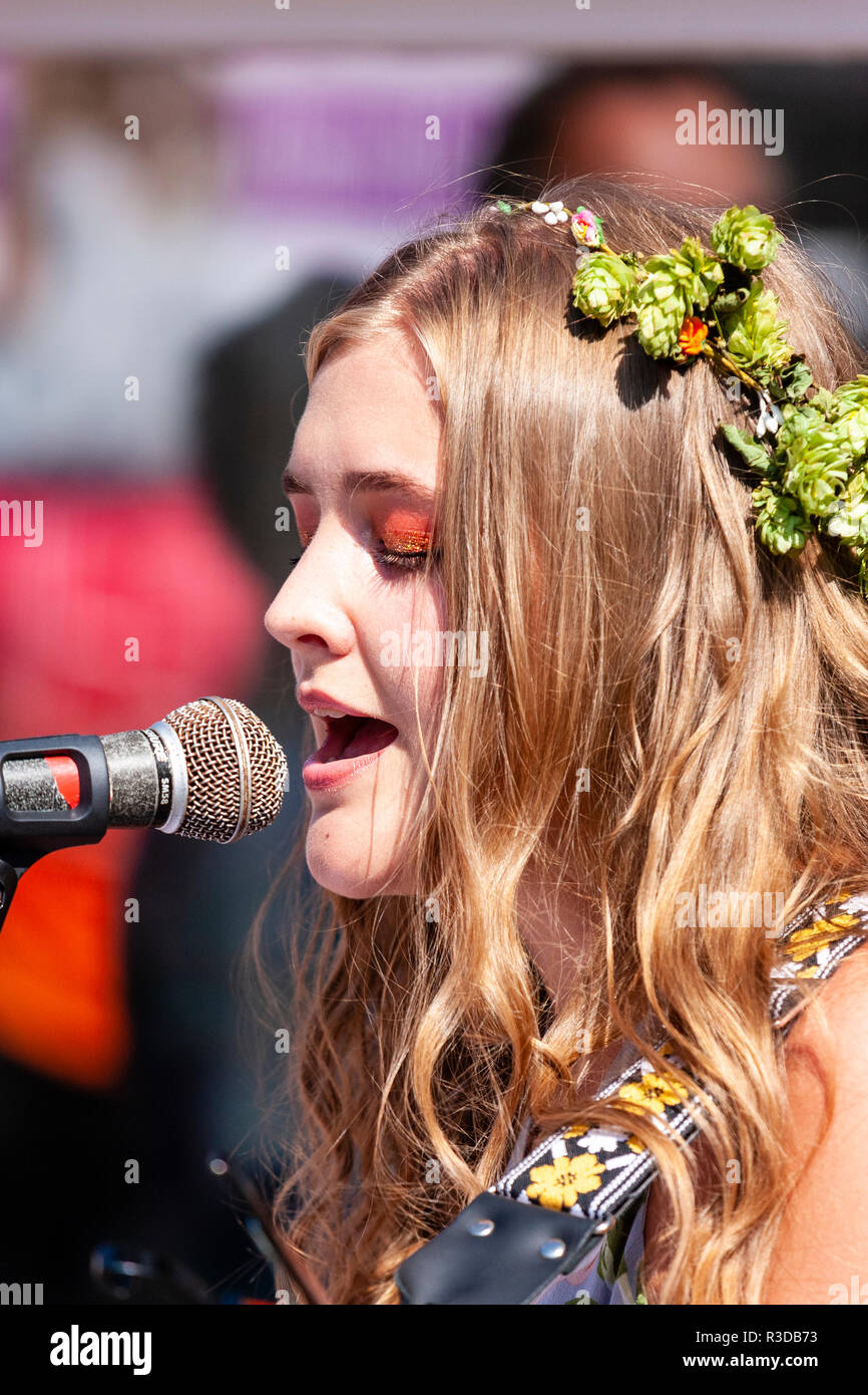 Faversham Hop Festival 2018. Maisy Beth, young Caucasian English singer songwriter, performing in the open air with garland of hops on head. Close up. - Stock Image