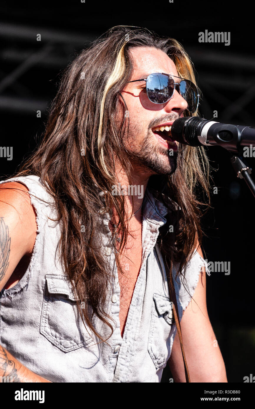 Faversham Hop Festival 201. Rock group Collateral UK performing on stage. Lead singer Angelo Tristan wearing sunglasses singing and playing guitar. - Stock Image