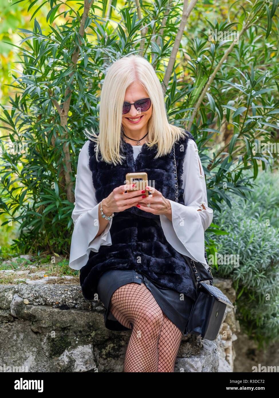 Attractive mid-adult senior pretty woman blonde hair outside sitting on stone wall holding hand writting sms message on smartphone looking down Stock Photo