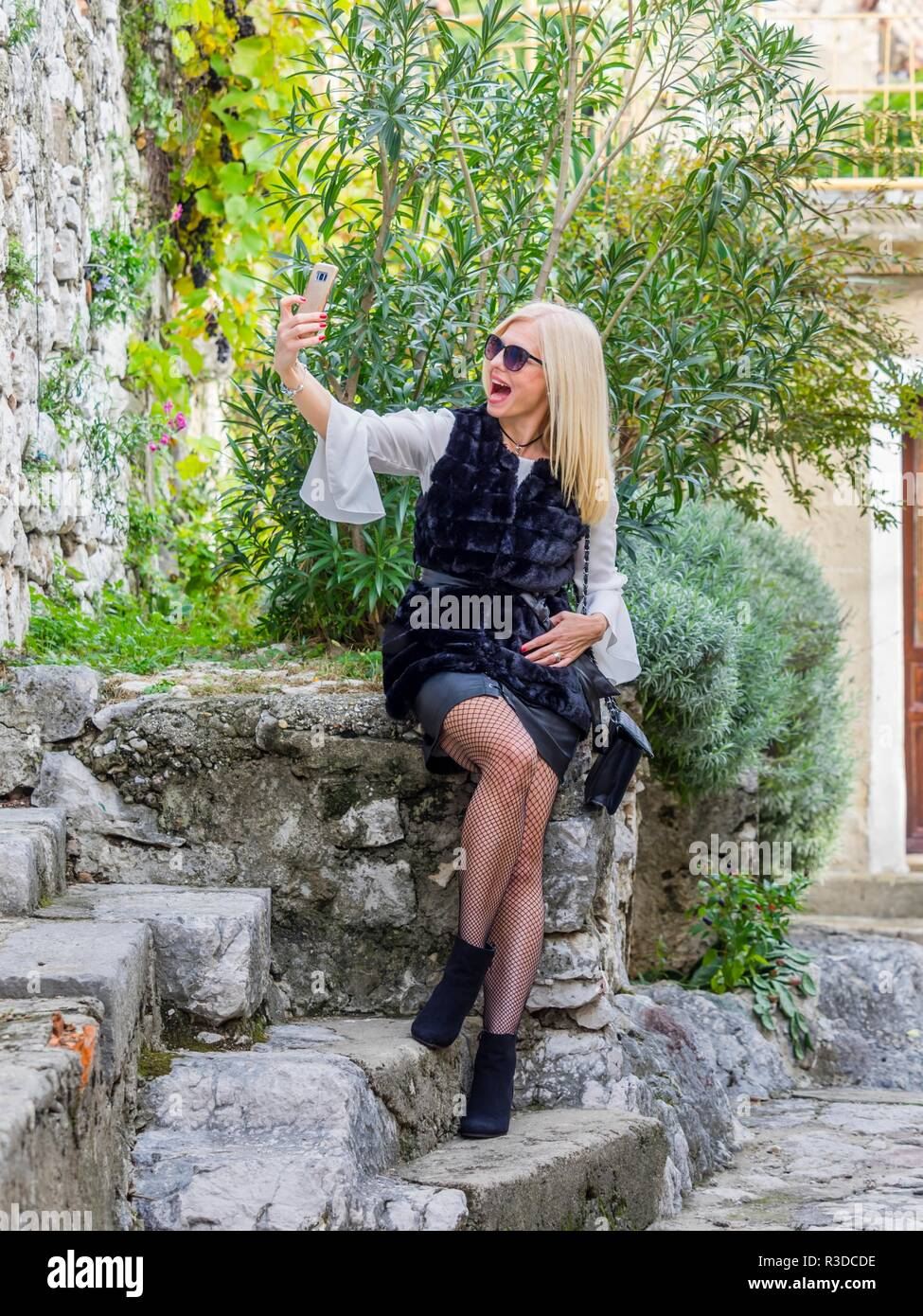 Attractive mid-adult senior pretty woman blonde hair outside sitting on stone wall taking self-portrait shoto selfie using smart-phone laughing Stock Photo