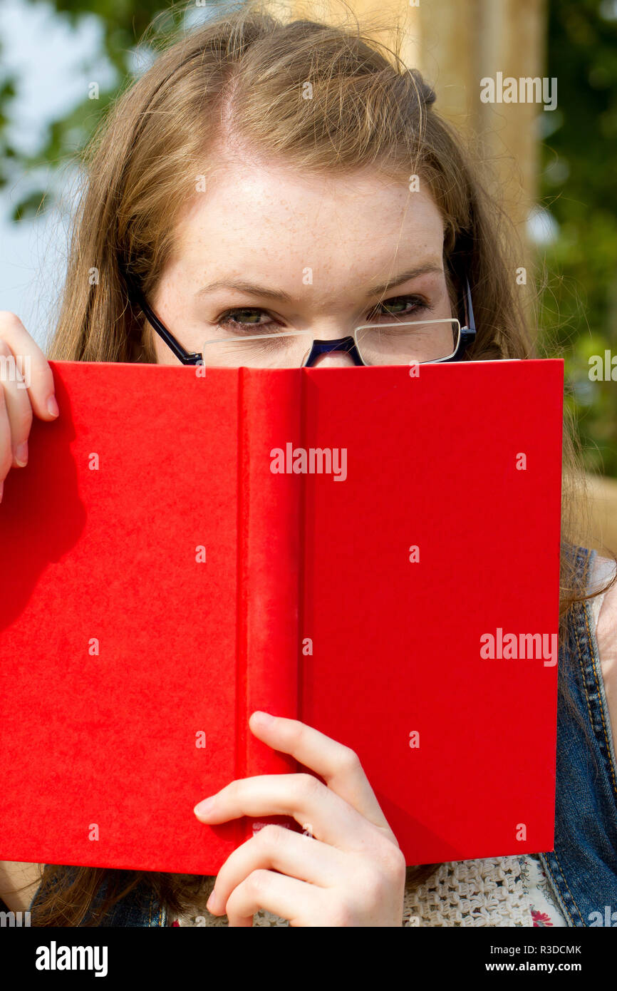 young woman with book in nature Stock Photo