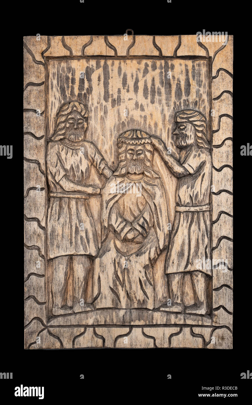 Naive or folk wood carving bas relief plaque representing the biblical crowning of Jesus with thorns subject. Isolated on black. - Stock Image