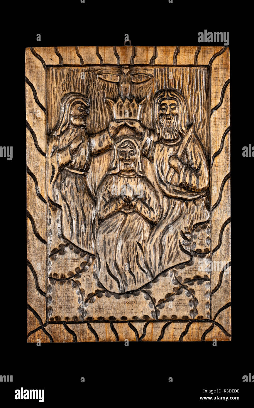 Naive or folk wood carving bas relief plaque representing the biblical Coronation of the Virgin or Coronation of Mary subject. Isolated on black. - Stock Image