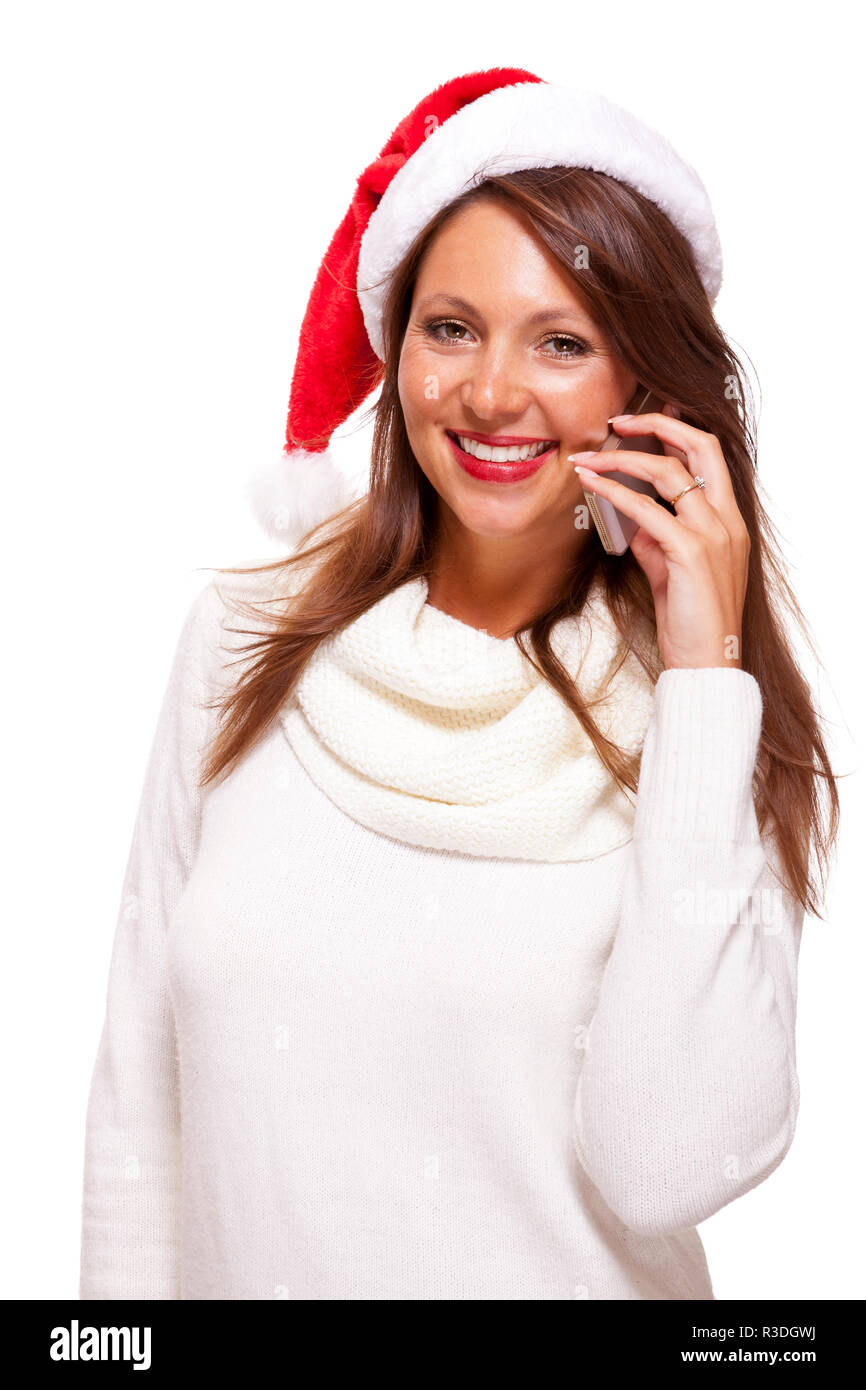 attractive woman with red santa claus hat reads a text message on her mobile phone and sent christmas wishes Stock Photo