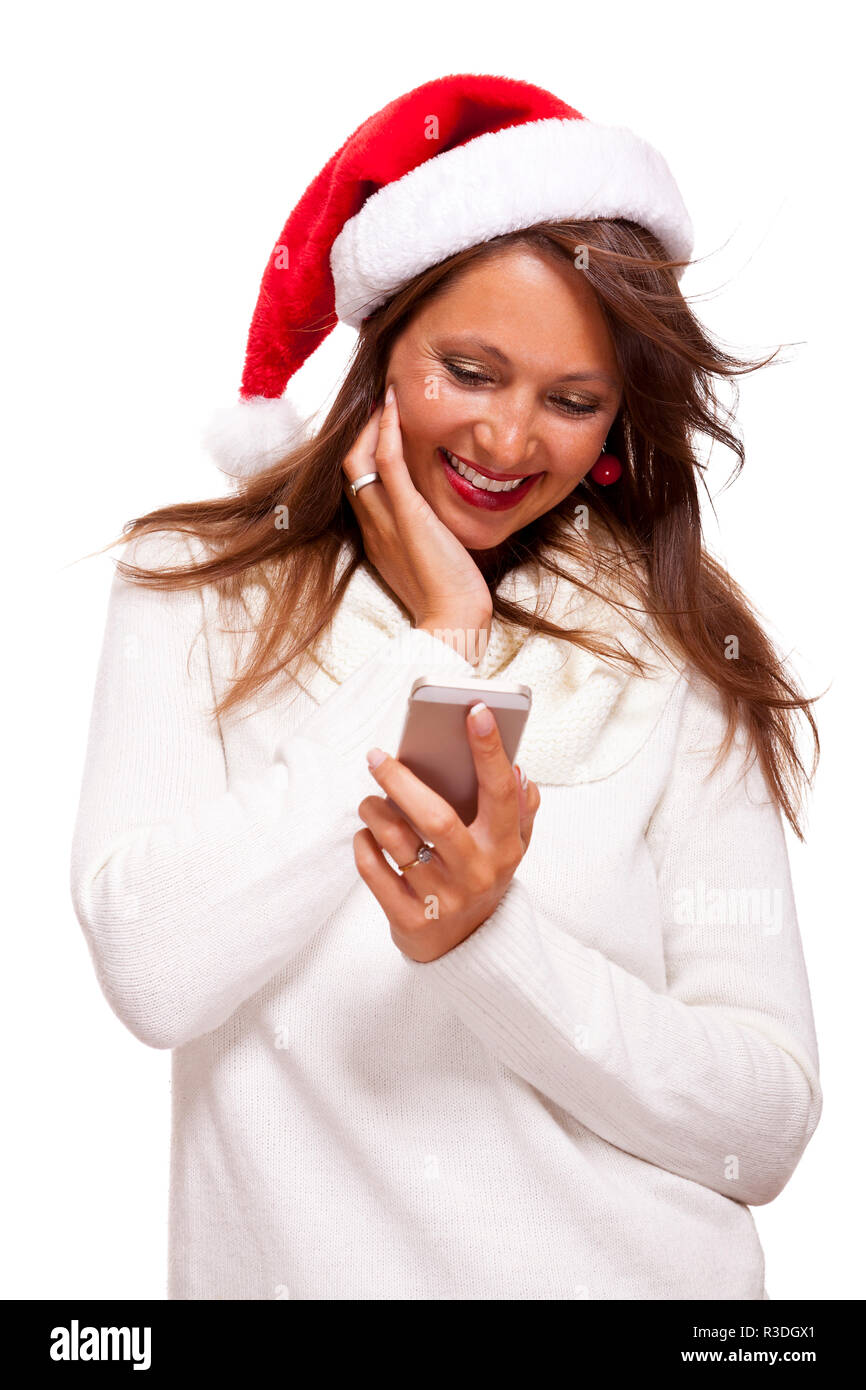 attractive woman with red santa hat reading a text message on her mobile phone and sent christmas wishes Stock Photo