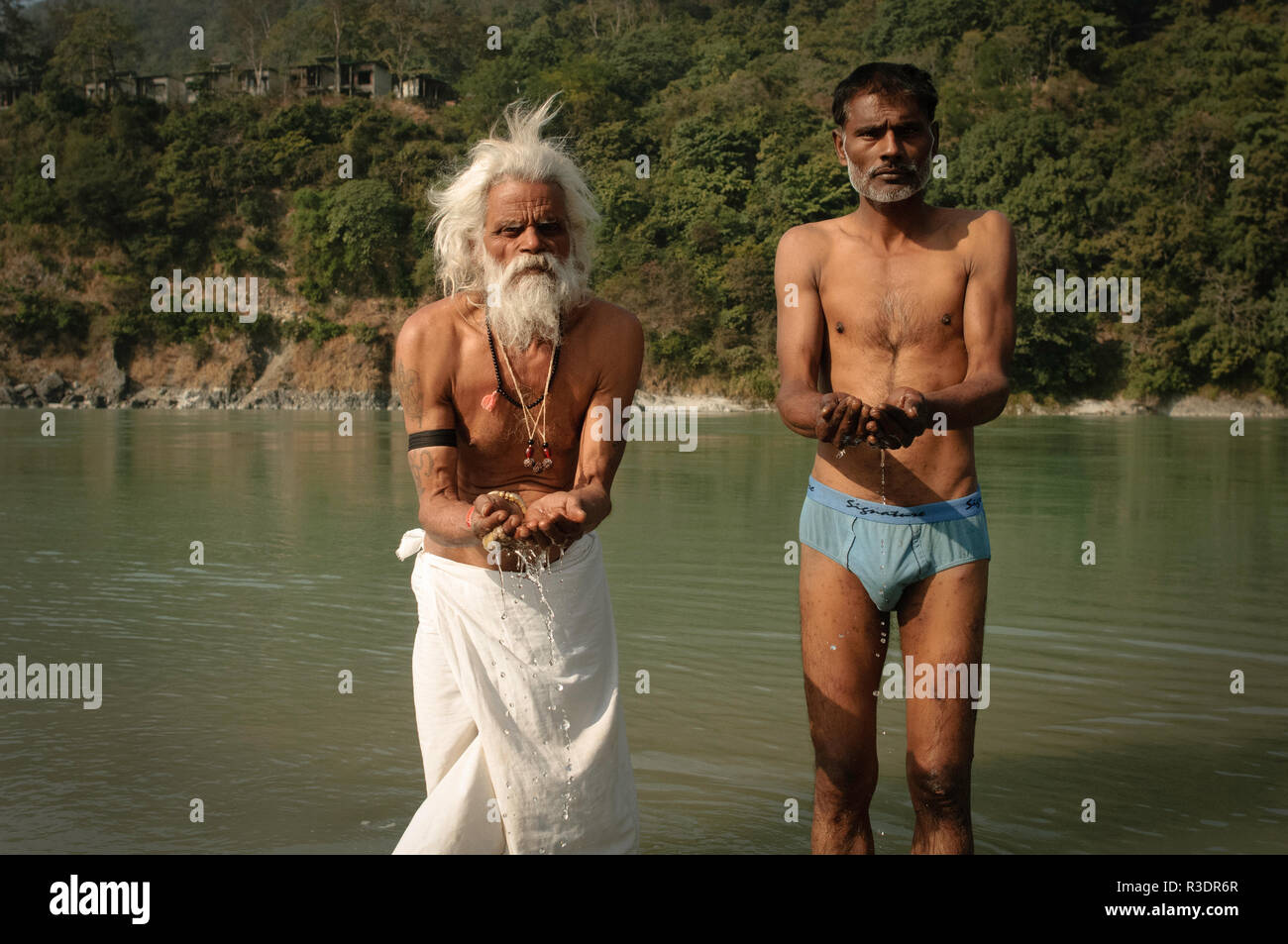 Sadhus taking a bath in the Holy Ganges river - Stock Image
