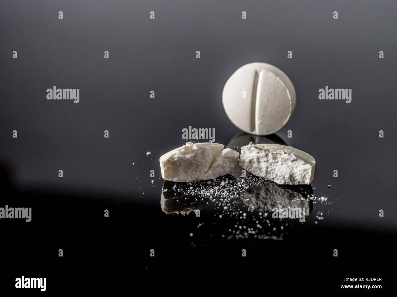 White pill by half isolated in black background, conceptual image - Stock Image