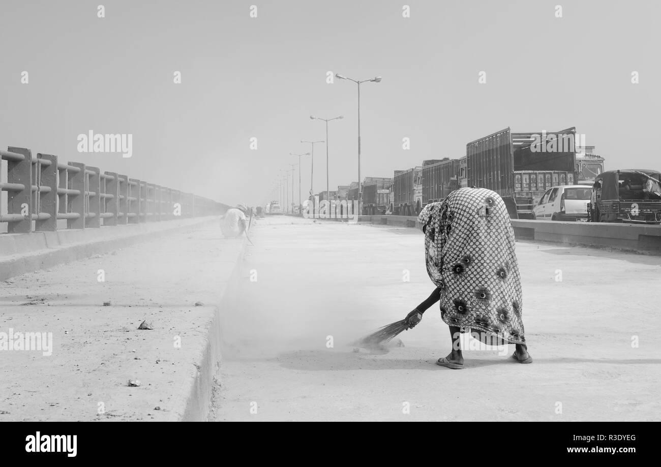 Woman sweeps one lane of the Mahatma Gandhi bridge during refurbishment and a long traffic jam on the other lane, Patna, Bihar, India. - Stock Image