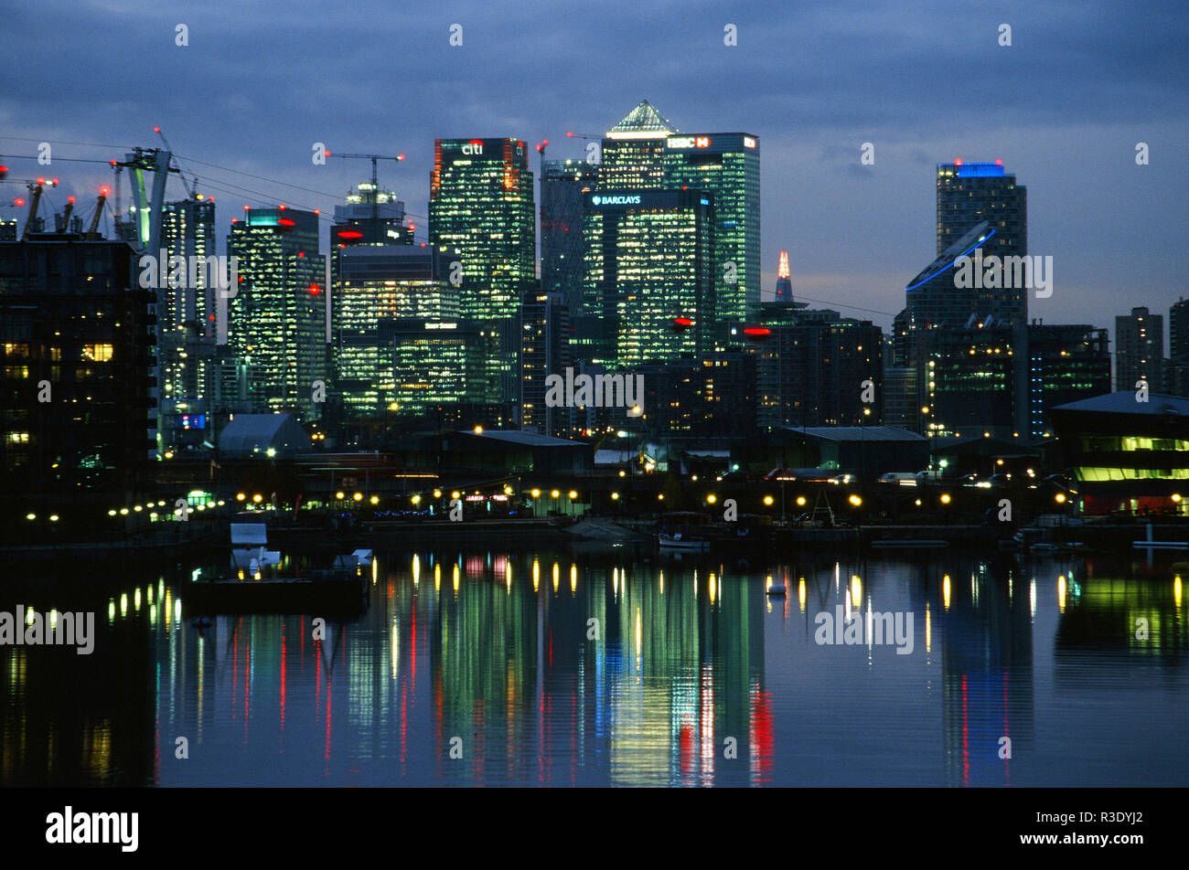 Buildings at Canary Wharf in the early evening, reflected in Royal Victoria Dock, Silvertown, East London UK - Stock Image