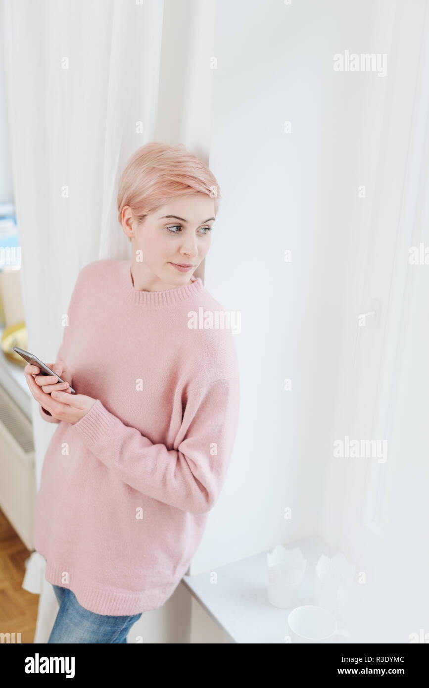 Thoughtful young woman staring out of a curtained window as she leans against the wall with her smartphone in her hands Stock Photo