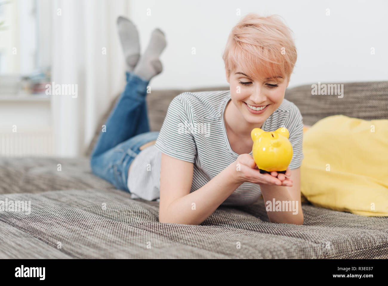 Cheerful young woman holding her piggy bank looking at it with a smile as she imagines what she can do with her savings as she lies on a sofa at home - Stock Image