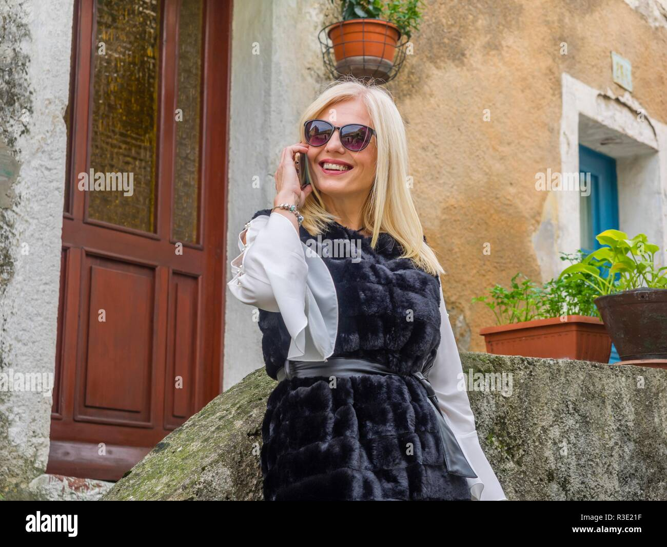 Attractive mid-adult senior pretty woman blonde hair outside standing inclined on wall smiling talking on cellphone holding hand using looking  away Stock Photo
