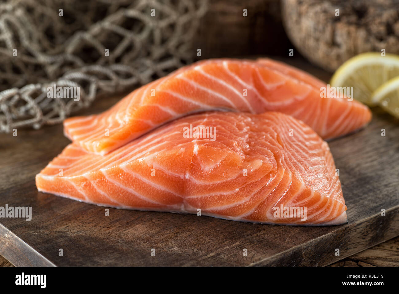 Fresh raw salmon fillets on a wooden board with lemon and fish net background. - Stock Image