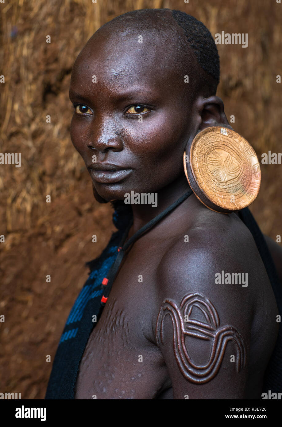 Portrait of a suri tribe woman with enlarged earlobes and huge earrings, Omo valley, Kibish, Ethiopia - Stock Image