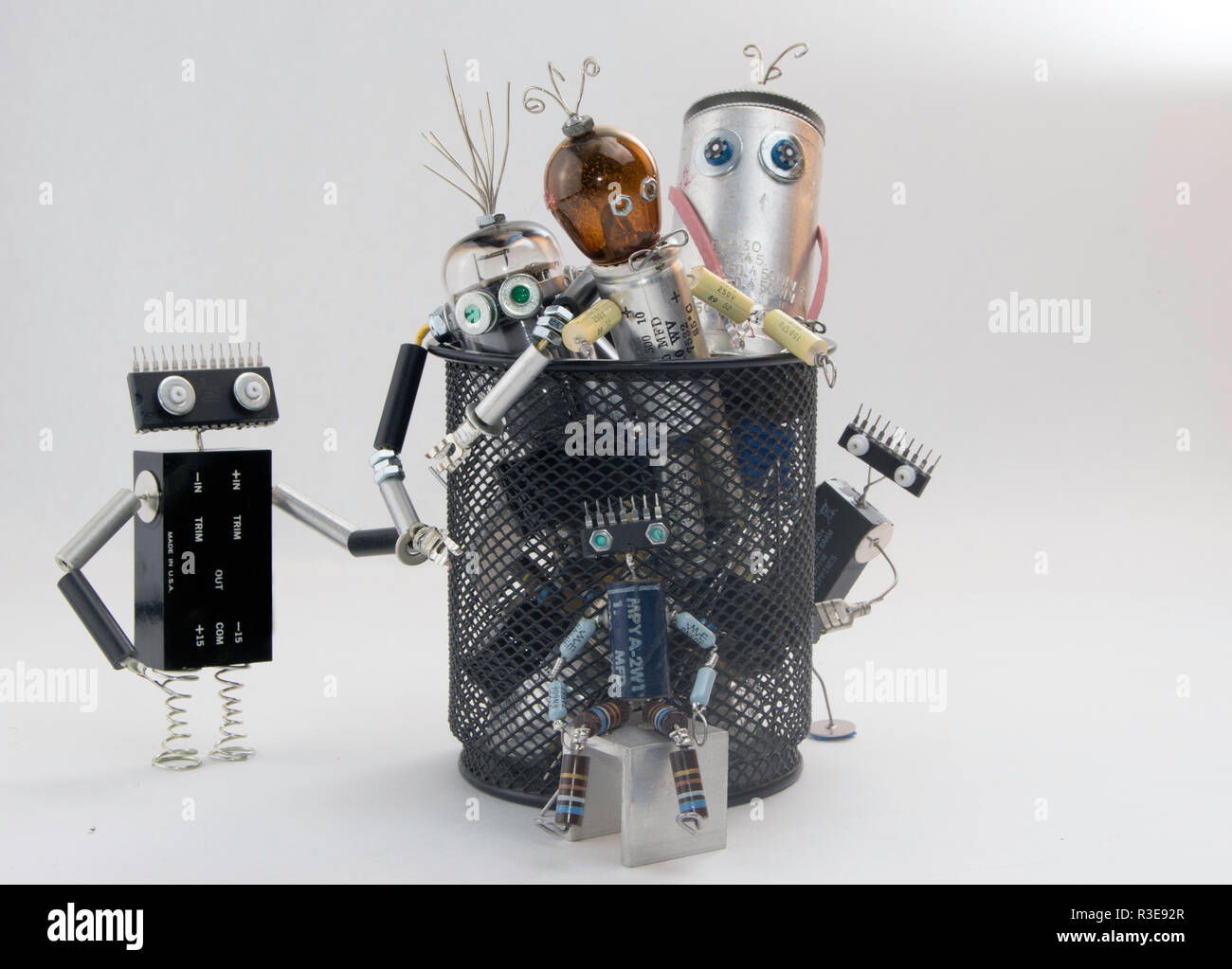electronic waste robot characters in trash can - Stock Image