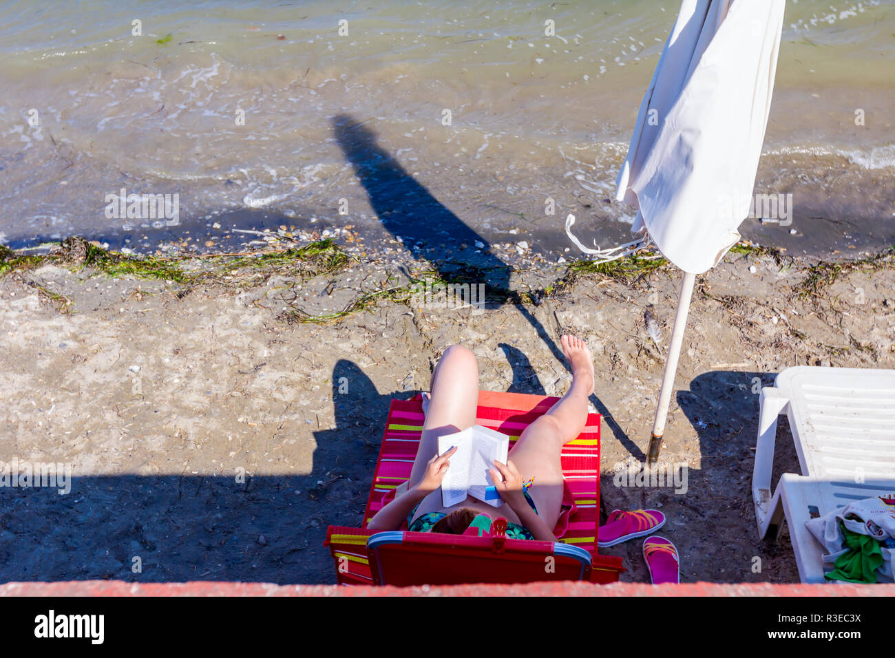 Woman sitting carefree in deckchair and she reading a book in sunshade next to the coastline, beach. - Stock Image
