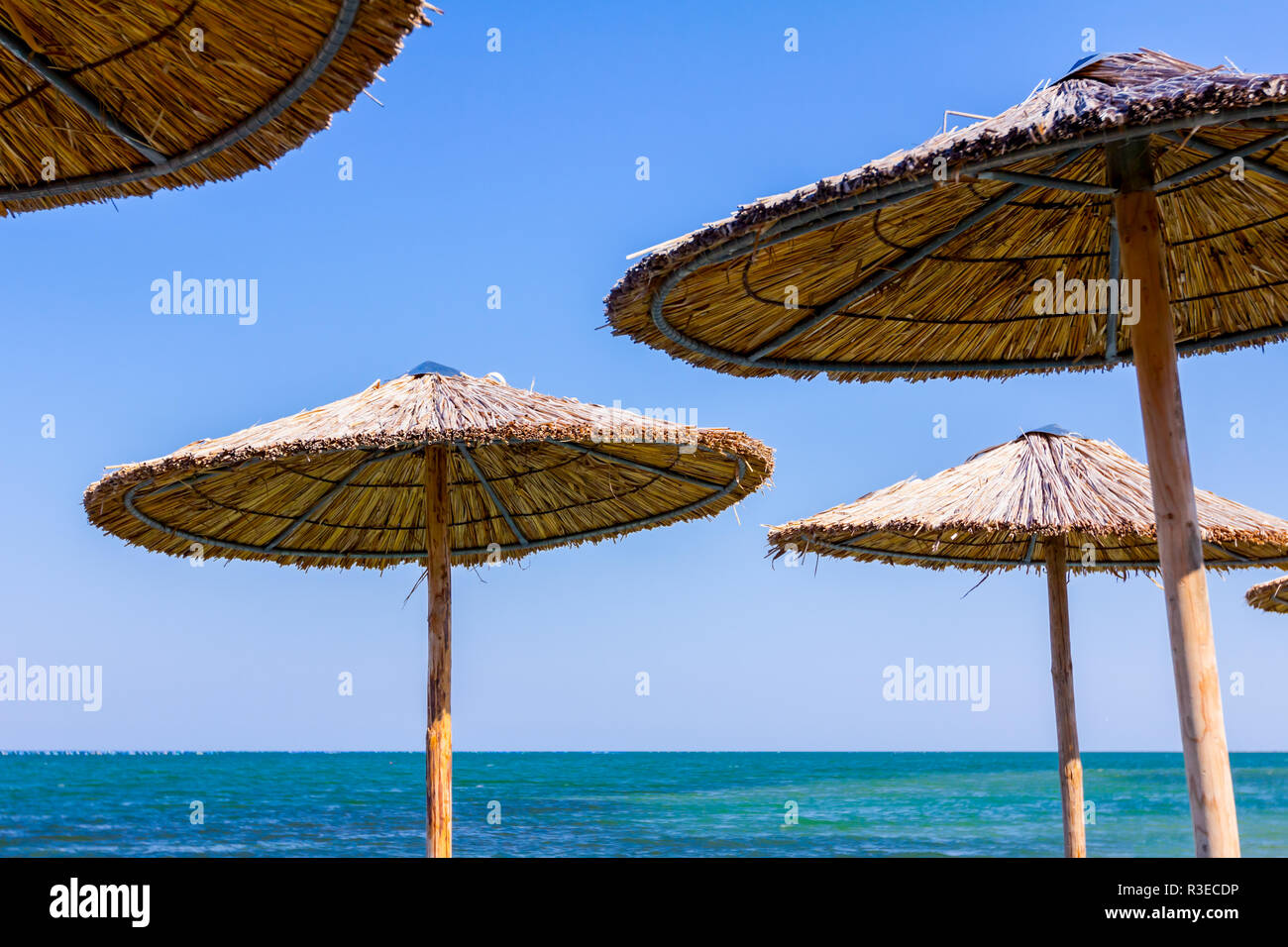 View On Blue Sea Below Thatched Beach Umbrella Over Blue Sky Sunshade Made With Wood And Reed On Seascape