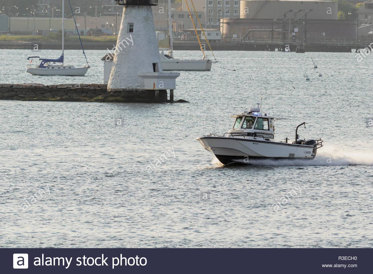Fairhaven, Massachusetts, USA - August 31, 2018: Fairhaven harbormaster patrol boat hurrying past Palmer Island Light Station on hazy summer evening - Stock Image