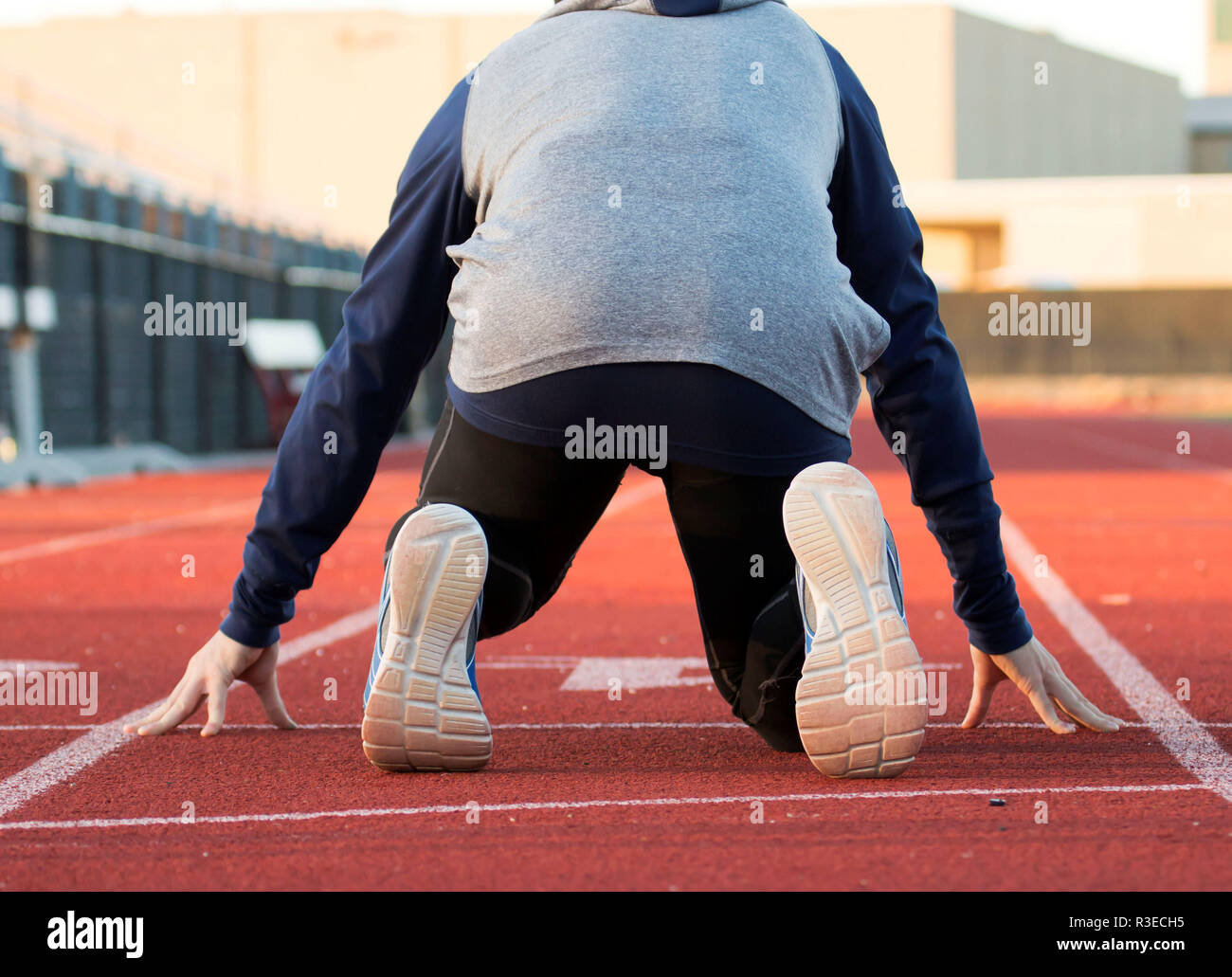A sprinter training for track and field, is in the on your mark position ready to run the 100 meter dash - Stock Image