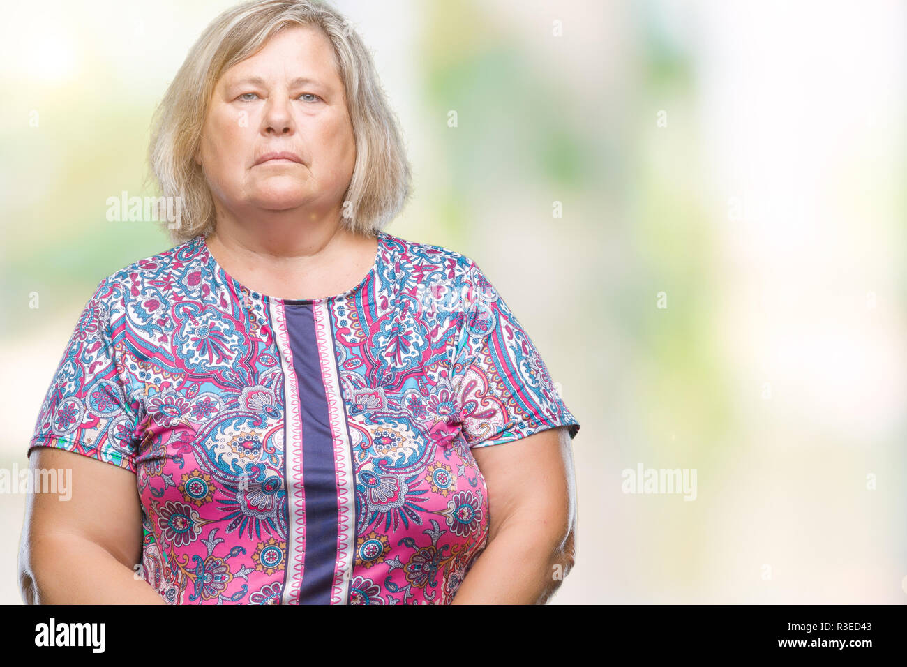 Senior plus size caucasian woman over isolated background with serious expression on face. Simple and natural looking at the camera. - Stock Image