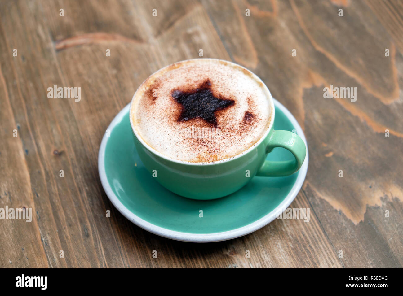 Cup of cappuccino coffee with a Christmas star design of chocolate sprinkled on frothy milk in green cup & saucer on wooden table  UK  KATHY DEWITT - Stock Image
