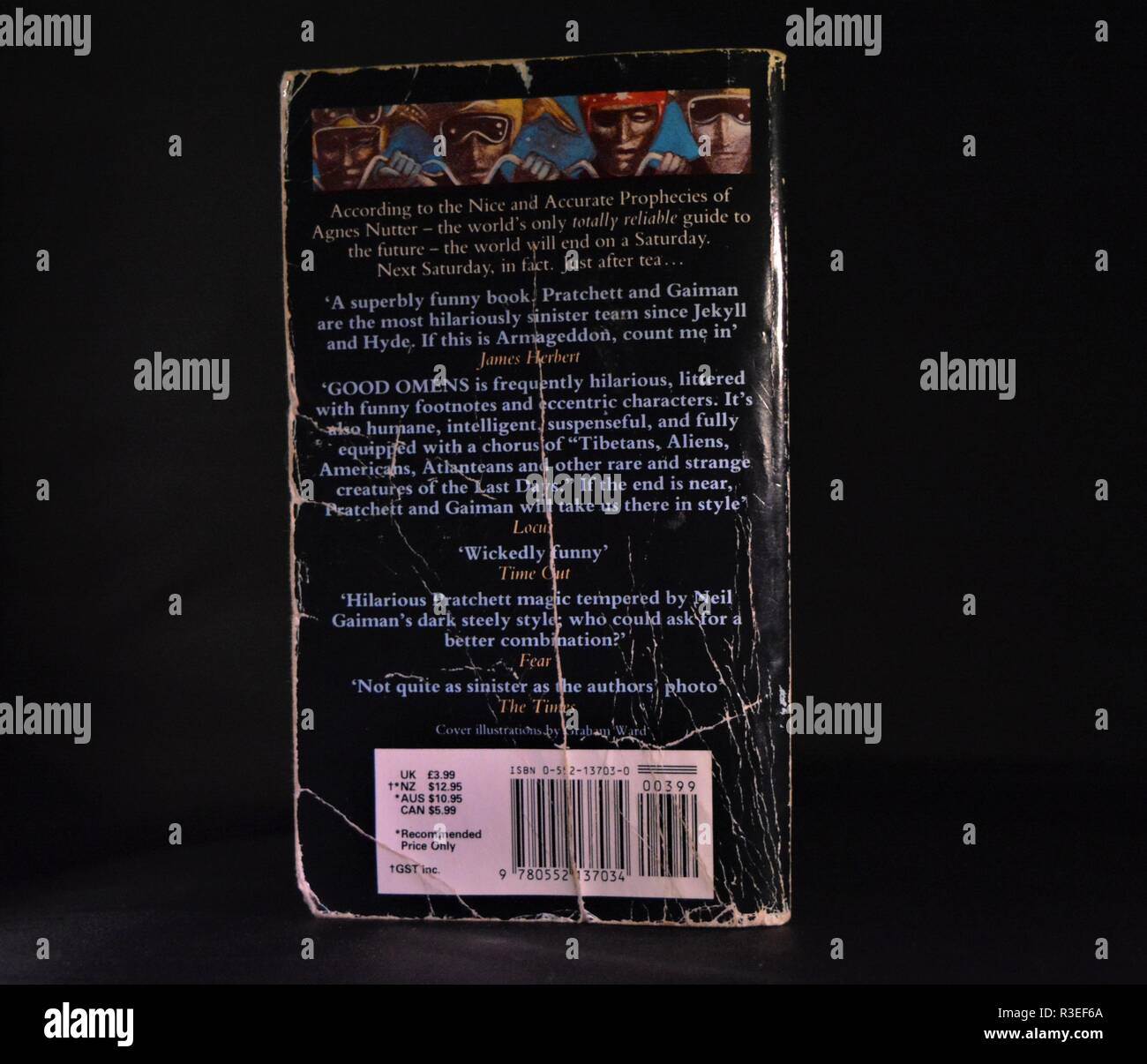 dog eared well worn paperback book , good omens, on dark background. - Stock Image