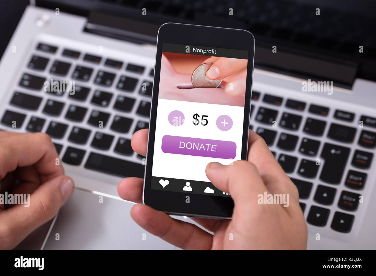 Man's Hand Donating Money On Mobile Phone Over Laptop - Stock Image