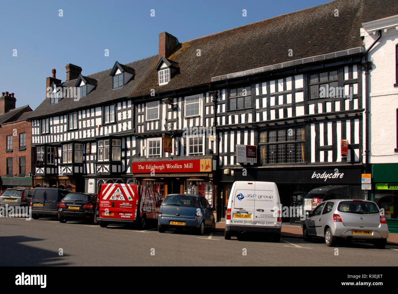 Row of shops, High Street, Bridgnorth, Shropshire, England, with parked vehicles in front - Stock Image