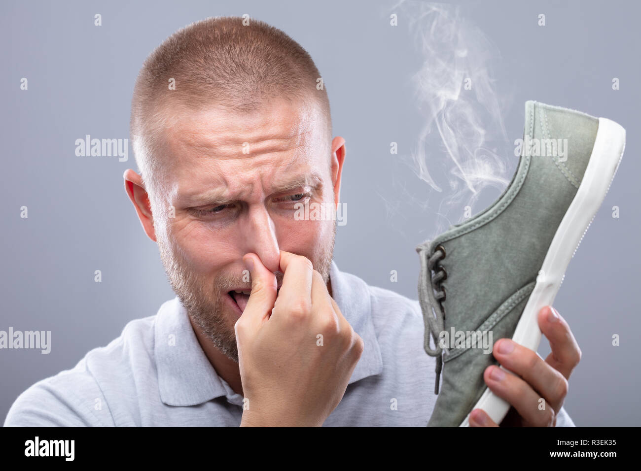 Close-up Of A Man Covering His Nose While Holding Stinky Shoe On Grey Background - Stock Image