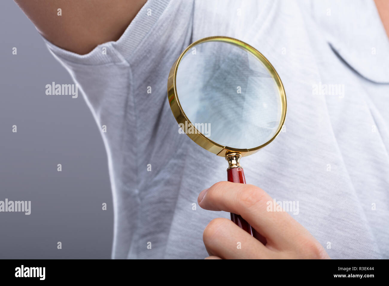Close-up Of A Man Looking At Sweaty Armpit Through Magnifying Glass - Stock Image