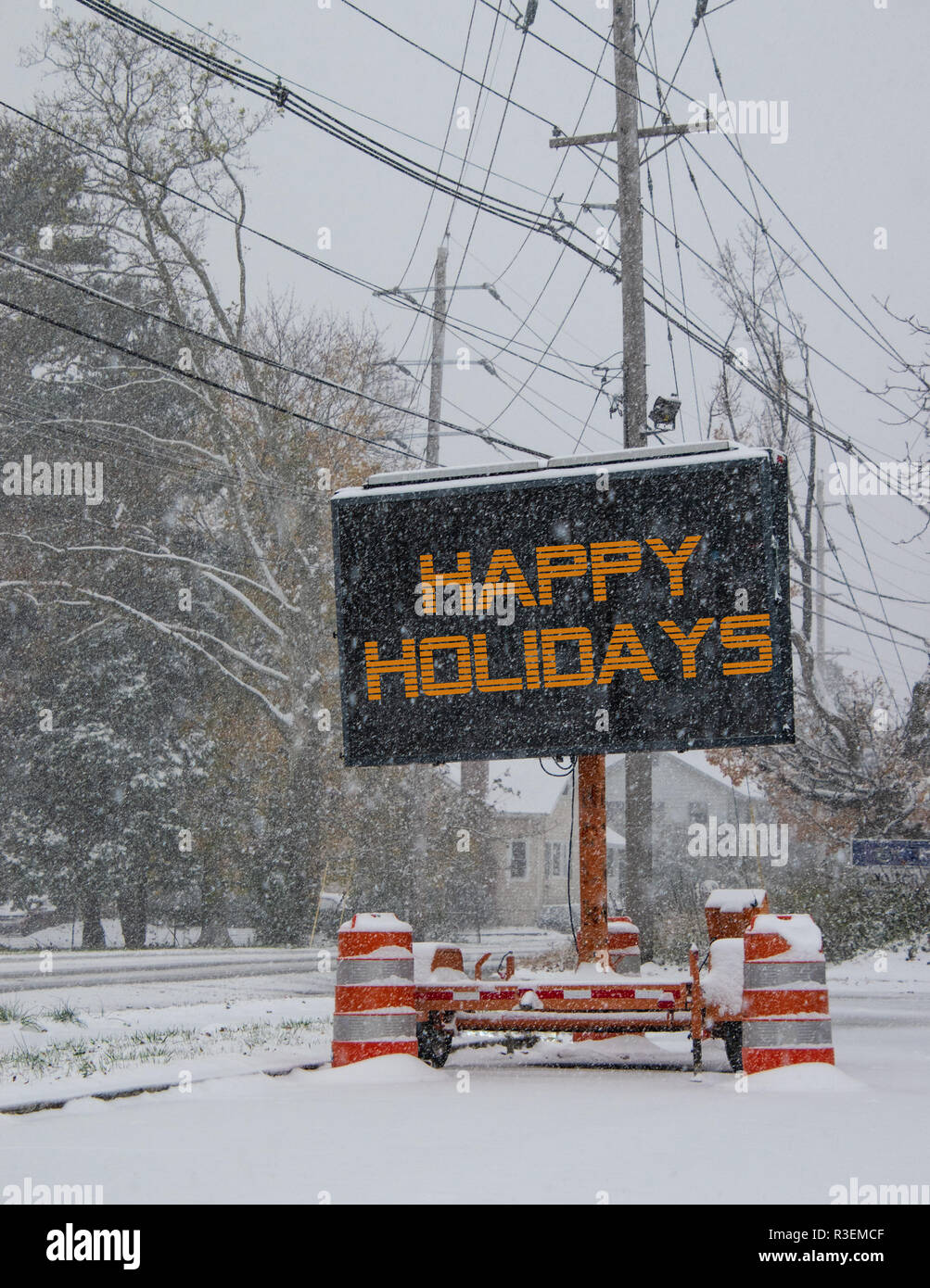 Electric road traffic mobile sign by the side of a snow covered road with snow falling that says, Happy Holidays - Stock Image