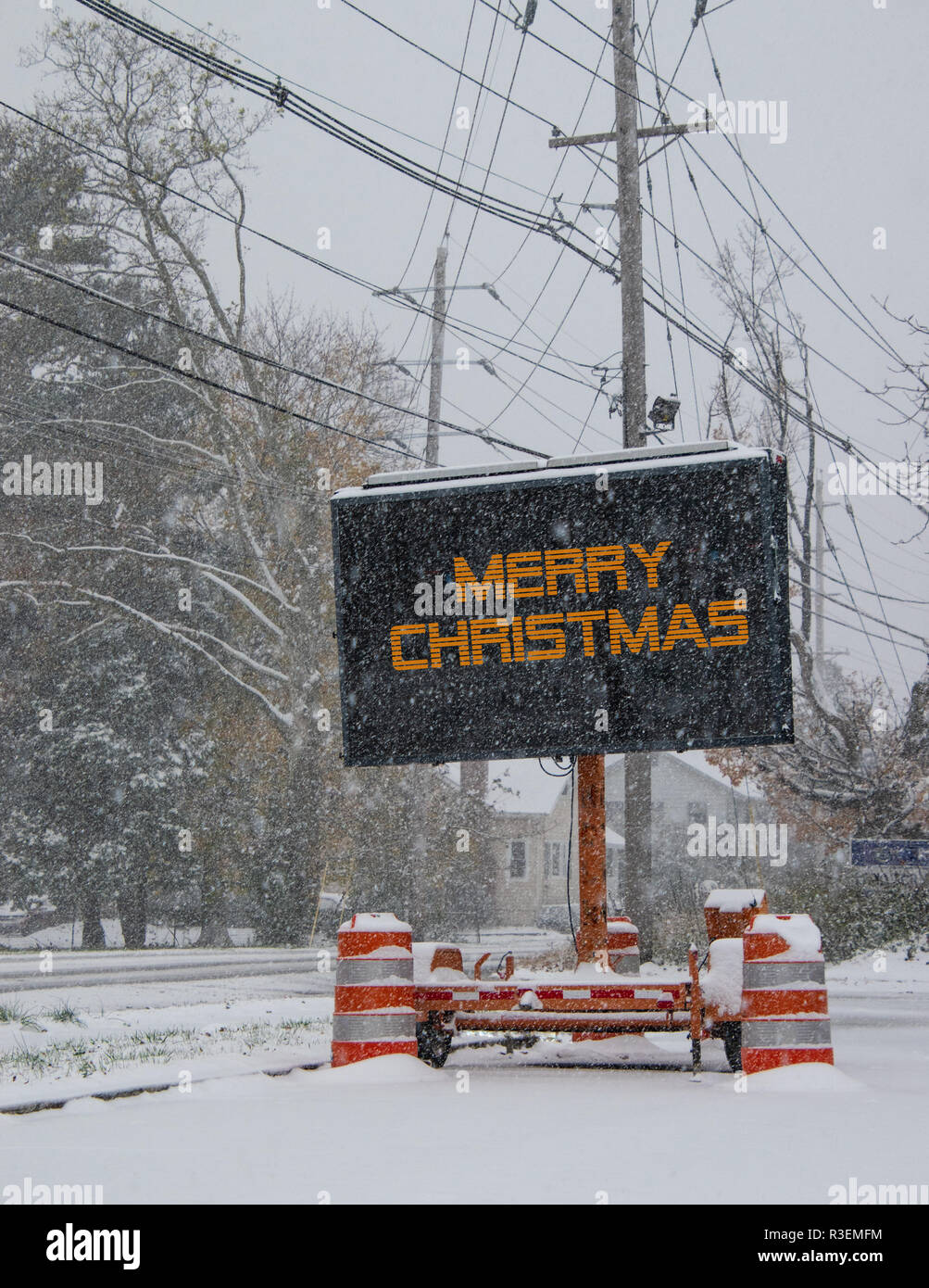 Electric road traffic mobile sign by the side of a snow covered road with snow falling that says, Merry Christmas - Stock Image