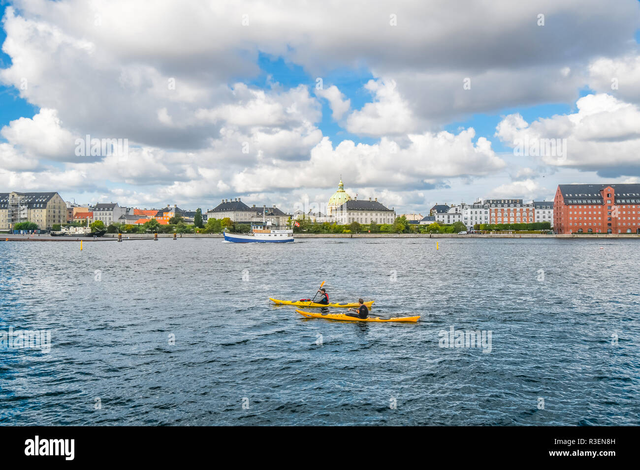 The dome of Frederik's Church, also known as the Marble Church rises above the city of Copenhagen as two kayakers float along a Danish canal. - Stock Image